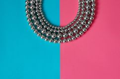 Silver beads on pink blue background. Silver beads lay on pink blue background Royalty Free Stock Image