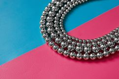 Silver beads on pink blue background. Silver beads lay on pink blue background Royalty Free Stock Images