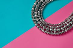 Silver beads on pink blue background. Silver beads lay on pink blue background Royalty Free Stock Photo