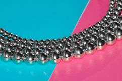 Silver beads on pink blue background. Silver beads lay on pink blue background Stock Images
