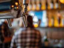Silver beer tap in restaurant bar with hard drinks and liquor in background stock photos
