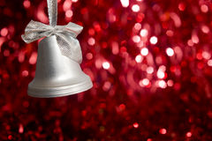Silver Bell Against Sparkly Red Background Stock Image