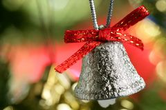 Silver bell in the christmas tree with red ribbon Stock Photos