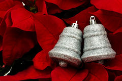Silver Bells. A set of silver bells sitting on a red flower background Stock Photos