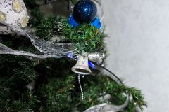 Silver bells on a fir. Christmas decorations. A silver ribbon on the green branches of a fir tree. Blue balls and two bells as decorations Royalty Free Stock Photography