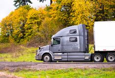 Silver big rig semi truck with dry van semi trailer going on autumn yellow trees on roadside. Profile of powerful silver big rig bonnet semi truck with dry van stock photo