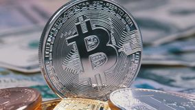 Silver Bitcoin Coin, BTC and Bills of Dollars are Rotating. Different Crypto Currency Close-up. Macro. Dollar banknotes of various denominations on which lies stock video footage