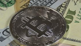 Silver Bitcoin Coin, BTC and Bills of Dollars are Rotating. Crypto Currency Close-up. Dollar banknotes of various denominations on which lies the stock video