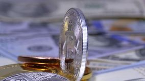 Silver Bitcoin Coin, BTC and Bills of Dollars are Rotating. Different Crypto Currency Close-up. Macro. Dollar banknotes of various denominations on which lies stock video