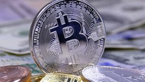 Silver Bitcoin Coin, BTC and Bills of Dollars are Rotating. Different Crypto Currency Close-up. Macro. Dollar banknotes of various denominations on which lies stock footage