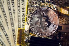 Silver bitcoin coin with dollars and computer motherboard, cryptocurrency mining and investing. Concept royalty free stock images