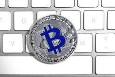 Silver bitcoin on computer keyboard. Digital currency. Silver bitcoin on computer keyboard, top view. Digital currency royalty free stock photos
