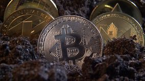 Silver bitcoin crypto currency coin in the dirt ground with others in the back: Litecoin, Ripple, Monerd, Ethereum coin. Digital. Currency, block chain market stock video footage