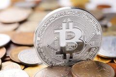 Silver Bitcoin exchange. Silver Bitcoin on different coins heap. Electronic money exchange concept stock photos