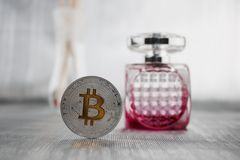 Silver bitcoin fragrance concept. Cryptocurrency physical silver bitcoin coin nerar pink fragrance Royalty Free Stock Image