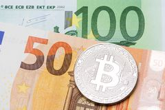 Silver bitcoin on hundred and fifty euro background. High resolution photo Royalty Free Stock Images