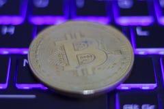 Silver bitcoin on illuminated computer keyboard.  stock photos