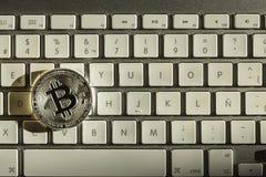 Silver bitcoin in keyboard. In sun closet stock image