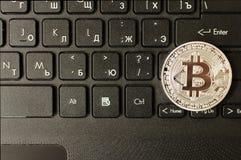 Silver bitcoin on keyboard. Silver bitcoin on laptop keyboard stock photo