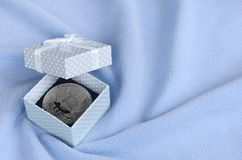 The silver bitcoin lies in a small blue gift box with a small bow on a blanket made of soft and fluffy light blue fleece fabric wi. Th a large number of relief stock photo