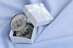 The silver bitcoin lies in a small blue gift box with a small bow on a blanket made of soft and fluffy light blue fleece fabric wi. Th a large number of relief Royalty Free Stock Photos