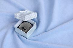 The silver bitcoin lies in a small blue gift box with a small bow on a blanket made of soft and fluffy light blue fleece fabric wi. Th a large number of relief royalty free stock images