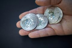 A silver Bitcoin is in the open hand. The coin shines and reflects light. The background is dark and abstract. The BTC currency is stock image