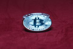 Silver bitcoin on a red background stock photography