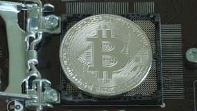 Silver Bitcoin virtual currency on a motherboard instead cpu. New metal cryptocurrency bitcoin on the circuit stock video