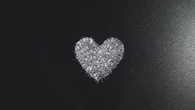 Silver blänker ordnar till hjärtaform på svart bakgrund med flygljus stock video