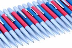 Silver-blått och silver-röda metallpennor på vit bakgrund Royaltyfri Bild