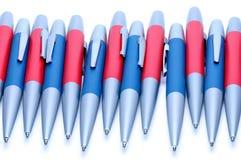 Silver-blått och silver-röda metallpennor på vit bakgrund Royaltyfria Foton