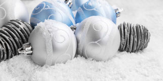 Silver and Blue Christmas Balls Decoration. Silver and Blue Christmas Balls in the Snow with Cones, Winter Holiday Decoration Royalty Free Stock Photography
