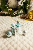 The Silver and blue Christmas balls and gifts on festive lighting background stock images
