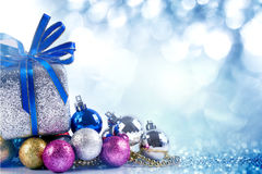 Silver and blue Christmas balls and gifts on blue lighting back royalty free stock photography