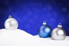 Silver and blue Christmas baubles on snow, blue background. Blue and silver Christmas baubles on snow with defocused blue lights in the background. Shallow depth Royalty Free Stock Images