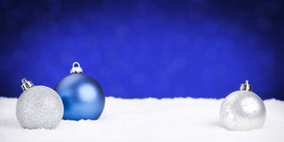 Silver and blue Christmas baubles on snow, blue background Royalty Free Stock Photo