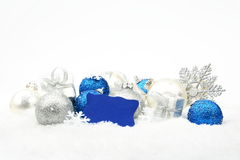 Silver and blue christmas decoration on snow with wishes card. Decoration of silver and blue christmas baubles and gifts with wishes card on snow white stock images