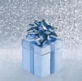 Silver blue gift box with ribbon over blurred shiny background Stock Images