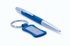 Silver-blue metal pen and keychain  on white Stock Photos