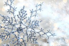 Silver blue snowflake 1. Silver blue snowflake against a shimmering background against a shimmering background Royalty Free Stock Images