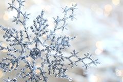 Silver blue snowflake. Against a shimmering background against a shimmering background Stock Photos