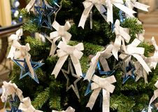 Silver blue star and a white ribbon on a festive Christmas tree, decoration element Christmas. And new year close-up stock image