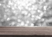 Silver Bokeh light with wooden table top for background. S Royalty Free Stock Photography