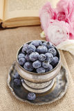 Silver bowl of blueberries, pink eustoma flowers in the backgrou Royalty Free Stock Image