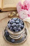 Silver bowl of blueberries, pink eustoma flowers in the backgrou Stock Photography