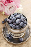 Silver bowl of blueberries, pink eustoma flowers in the backgrou Stock Photo
