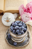 Silver bowl of blueberries, pink eustoma flowers in the backgrou Stock Image