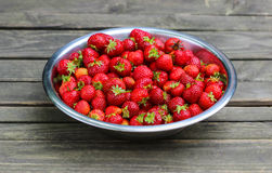 Silver bowl of strawberries on wooden table Stock Image