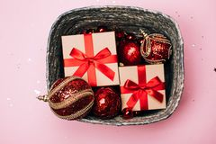 Silver box with presents and red christmas balls on pink pastel background. royalty free stock images